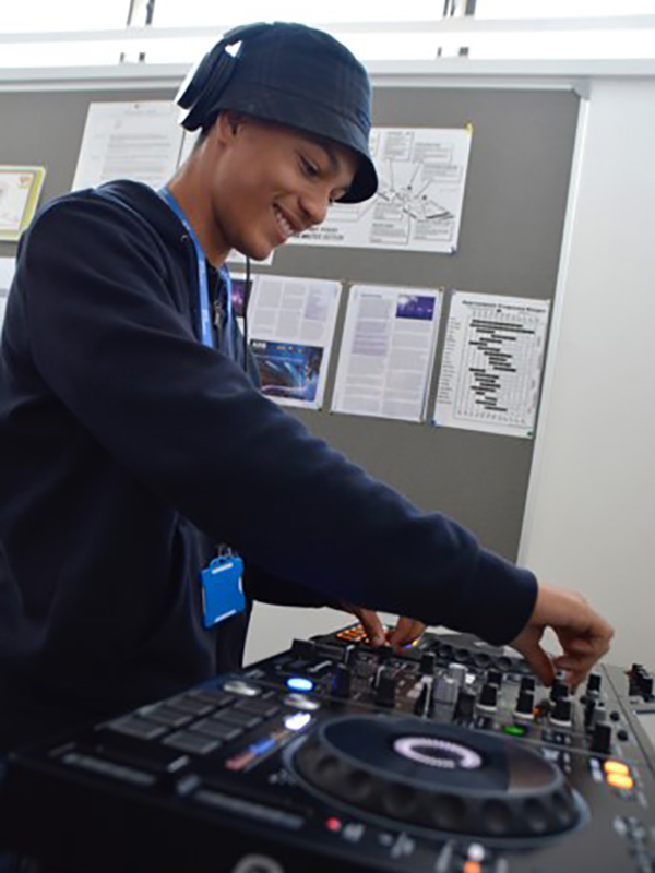 Music Technology student using a mixing deck