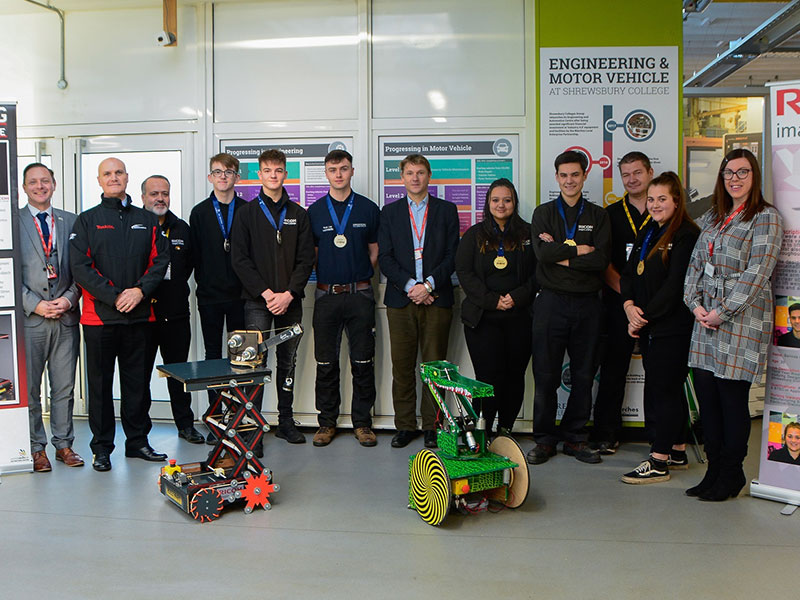 A group of apprentices, College staff, including the Principal and employers standing behind two robots