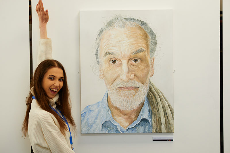 Female art student standing next to a large, lifelike portrait of a man with a beard.