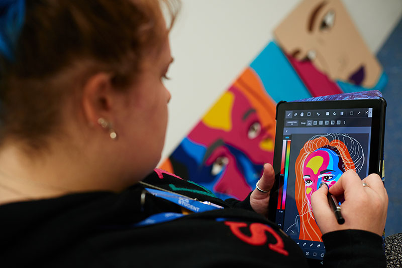 Female student drawing colourful graphical illustration of a woman using a tablet device.