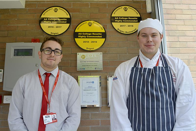 Studentsb Jack Earl and Jack Kirby standing in front of AA rosettes