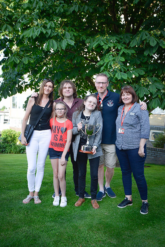 Guitarist Nick McCabe, Jon's wife and daughter and two music teachers standing next to student who is holding a silver trophy.