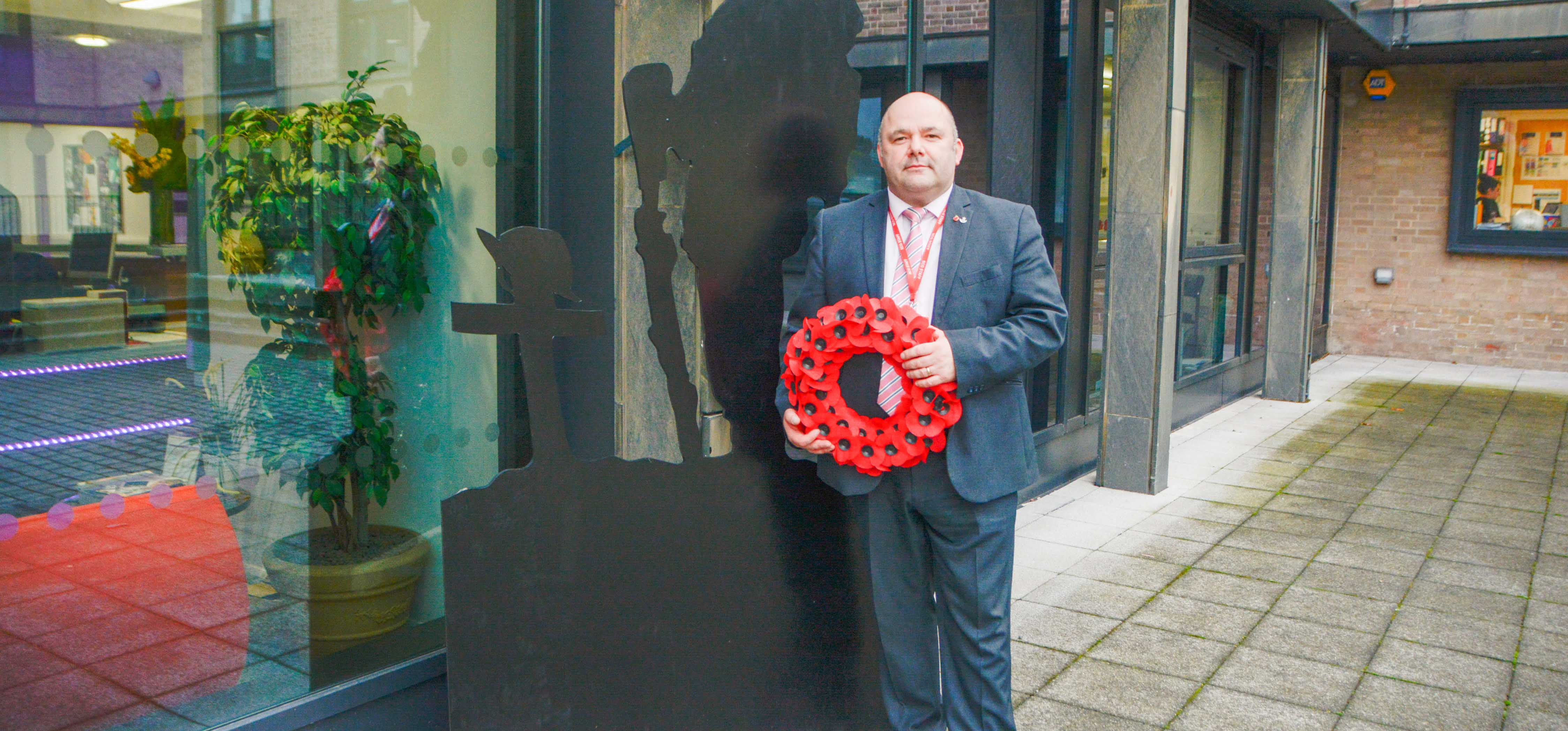 College Commercial Manager holding a poppy wreath and standing next to wooden silhouette of a soldier.