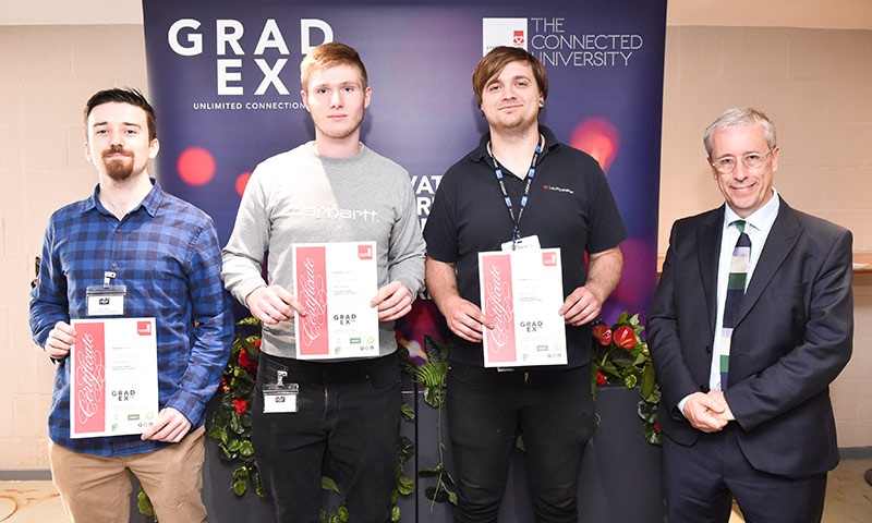 Three students holding certificates standing next to General Manager at Makita.
