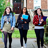 three female students walking from college with books