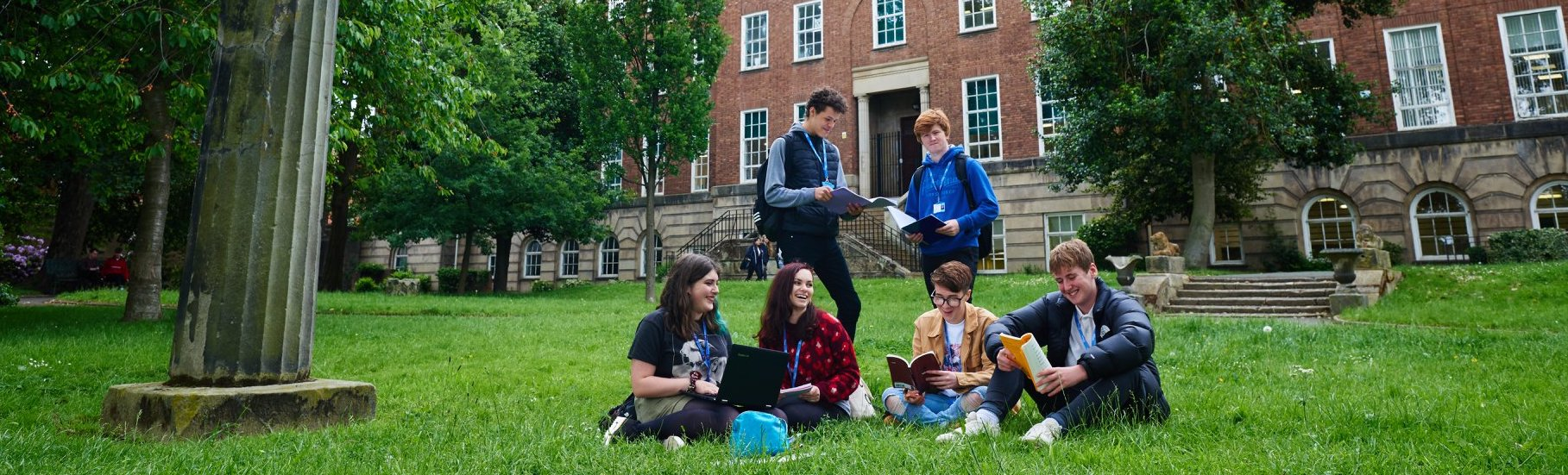 Students reading books on the college lawn