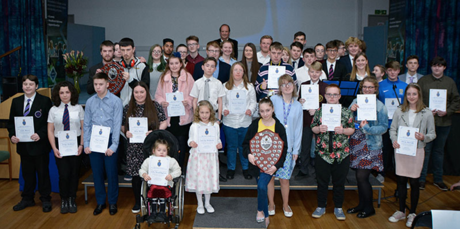 Group of young people at an awards event holding certificates