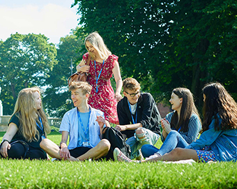 students sitting on grass in park