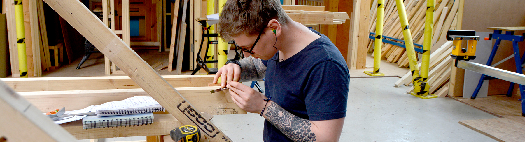 A student marking some timber ready to be cut