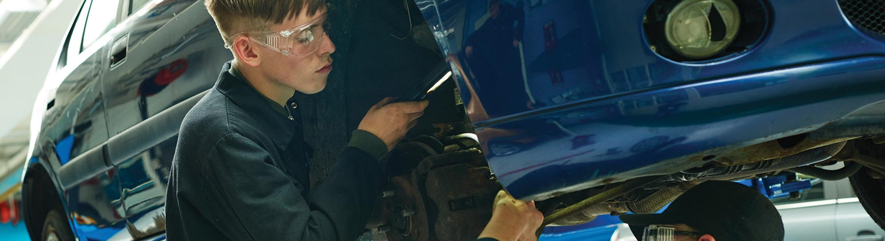 A student working on the side of a car